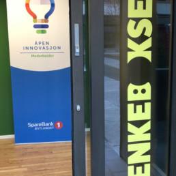 Inngangspartiet til «Tenkeboksen» – en dør med Tenkeboksens logo på. I bakgrunnen skimter man en roll-up som tilhører SpareBank1 Østlandet, med teksten «Åpen innovasjon – Medarbeider».